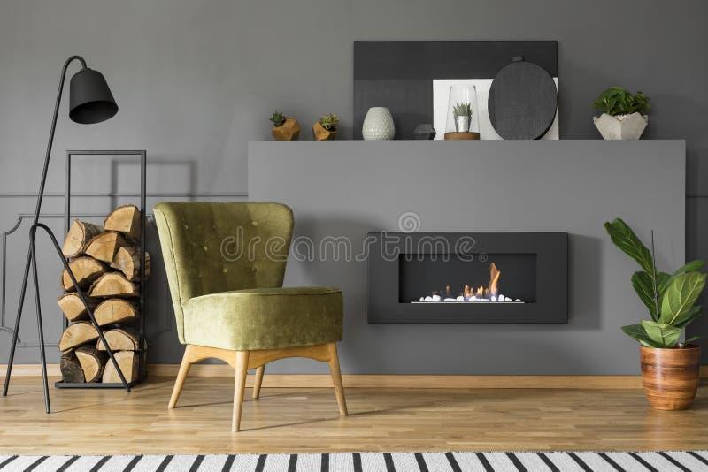 Fauteuil et bois de chauffage verts à côté de cheminée dans le roo vivant gris photographie stock