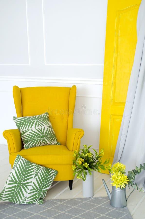 Fauteuil jaune dans l'intérieur avec des éléments des textiles à la maison, des oreillers et du décor floral image stock