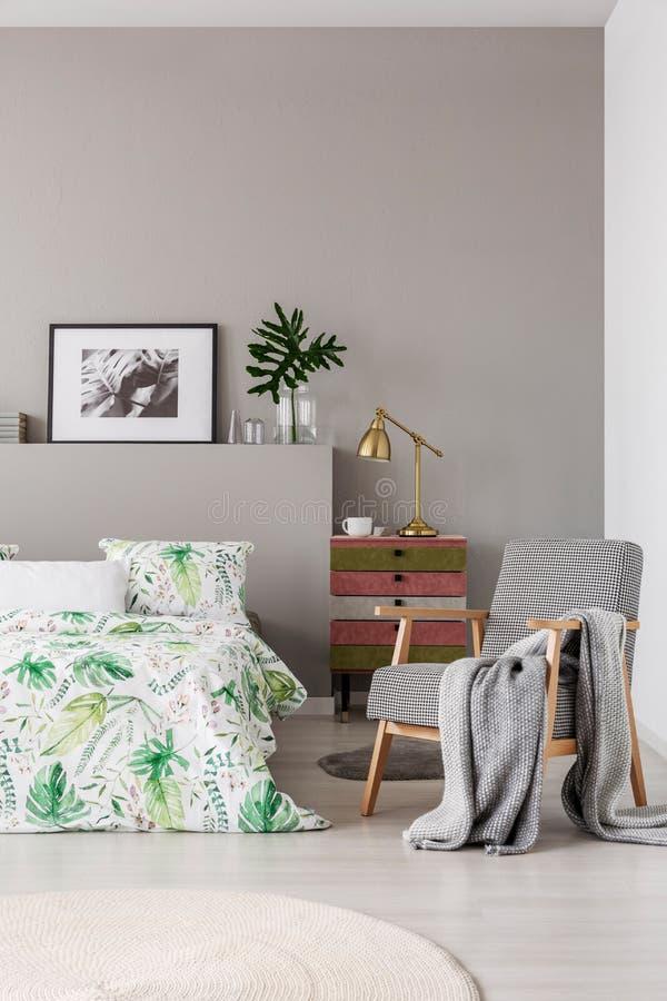 Fauteuil modelé avec la couverture grise dans la chambre à coucher à la mode intérieure avec le lit confortable avec la literie f image libre de droits