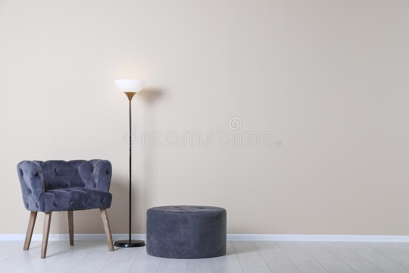 Fauteuil, pouf et lampe confortables près de mur avec l'espace pour le texte Élément intérieur image libre de droits