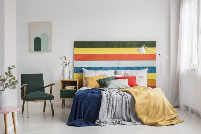 Fauteuil rétro dans un décor moderne avec tête de lit arc-en-ciel images stock