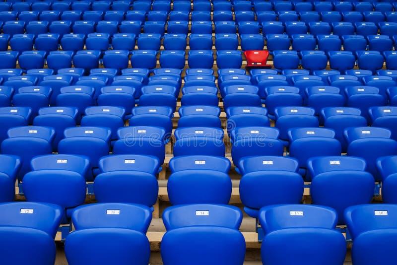 Fauteuil rouge dans une rangée des fauteuils bleus Soyez différent Soyez specia images stock