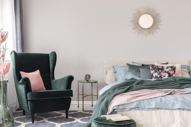 Fauteuil vert vert avec l'oreiller rose en pastel à côté de la table élégante de nightstand avec l'horloge dans l'intérieur à la  photos stock