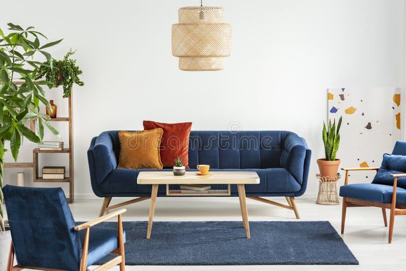 Fauteuils et divan en bois bleus dans l'intérieur de salon avec les usines et la table ci-dessus de lampe Photo réelle photographie stock libre de droits