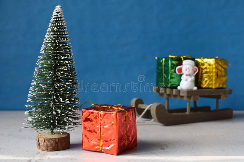Faux Christmas tree and gifts on little sleigh. Happy New Year and Merry Christmas concept.Greeting card or festive background. Copy space royalty free stock image