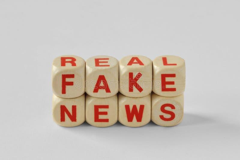 Faux de mots et vraies actualités écrits avec les cubes en bois photo stock