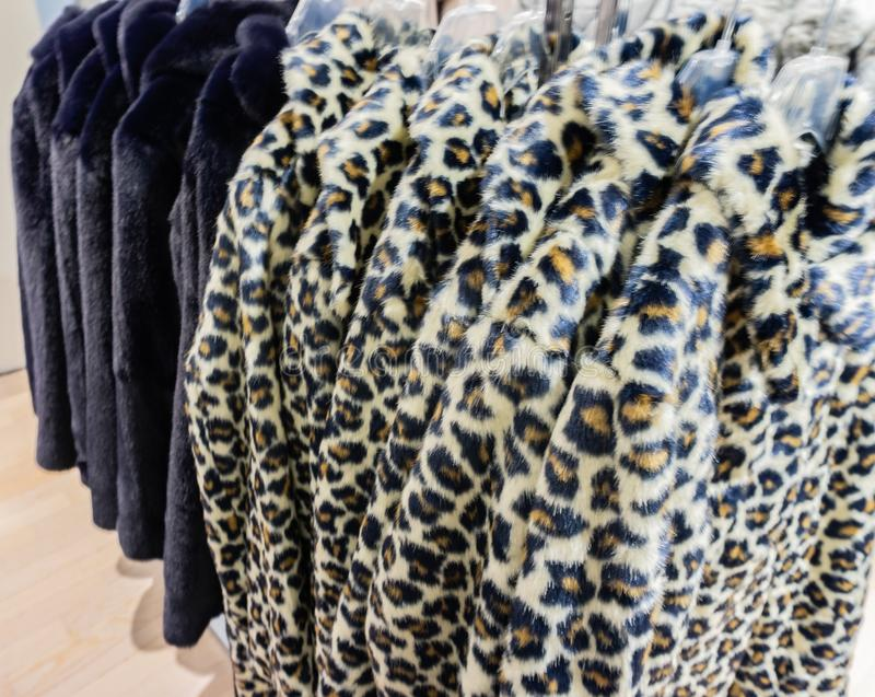 Faux fur jacket for winter season on a clothes rack.  royalty free stock photo