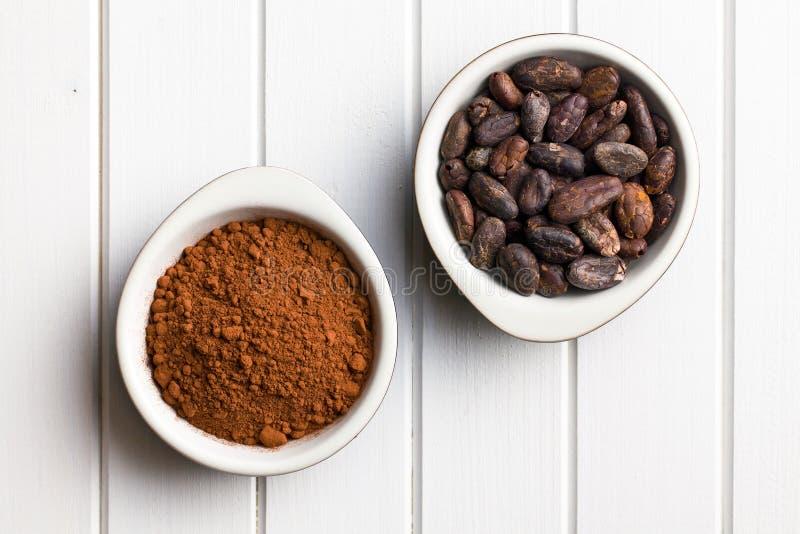 Fave e cacao in polvere di cacao in ciotole fotografia stock libera da diritti