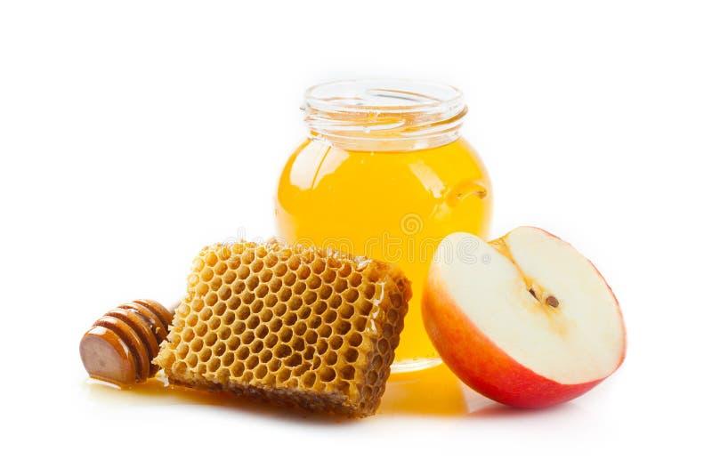 Favo de mel, um frasco do mel e uma fatia de maçã imagem de stock