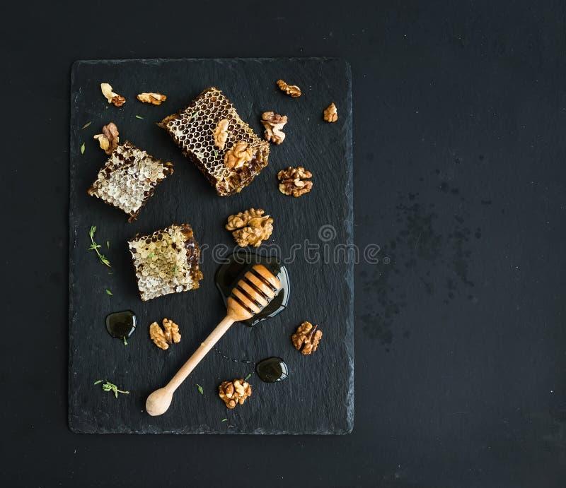 Favo, noci e merlo acquaiolo del miele sull'ardesia nera immagini stock