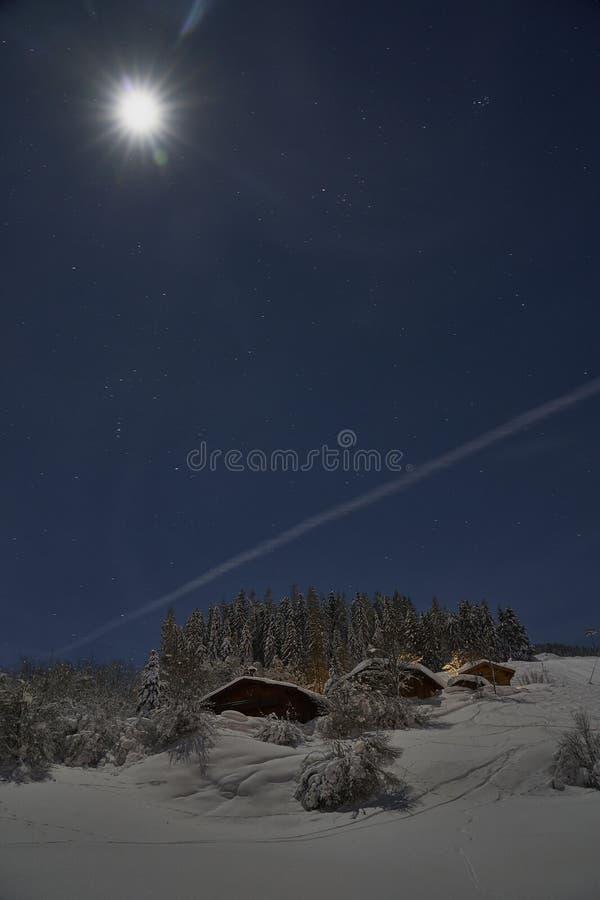 Favola di notte di inverno della luna piena, cottage sotto molta neve fotografia stock libera da diritti