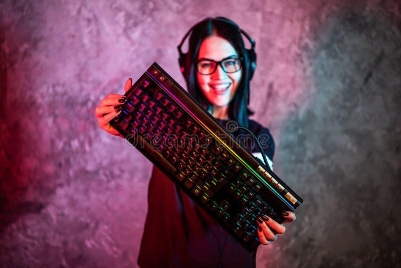 Favorable muchacha amistosa hermosa que presenta con un teclado en sus manos, vidrios que llevan de la flámula del videojugador M foto de archivo libre de regalías