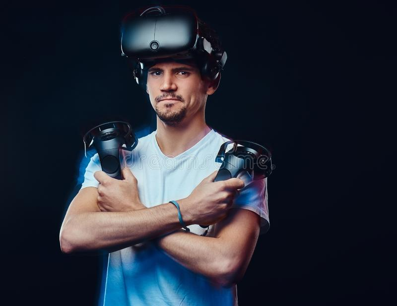 Favorable videojugador serio que lleva los vidrios de la realidad virtual y las palancas de mando de los controles, presentando c fotografía de archivo