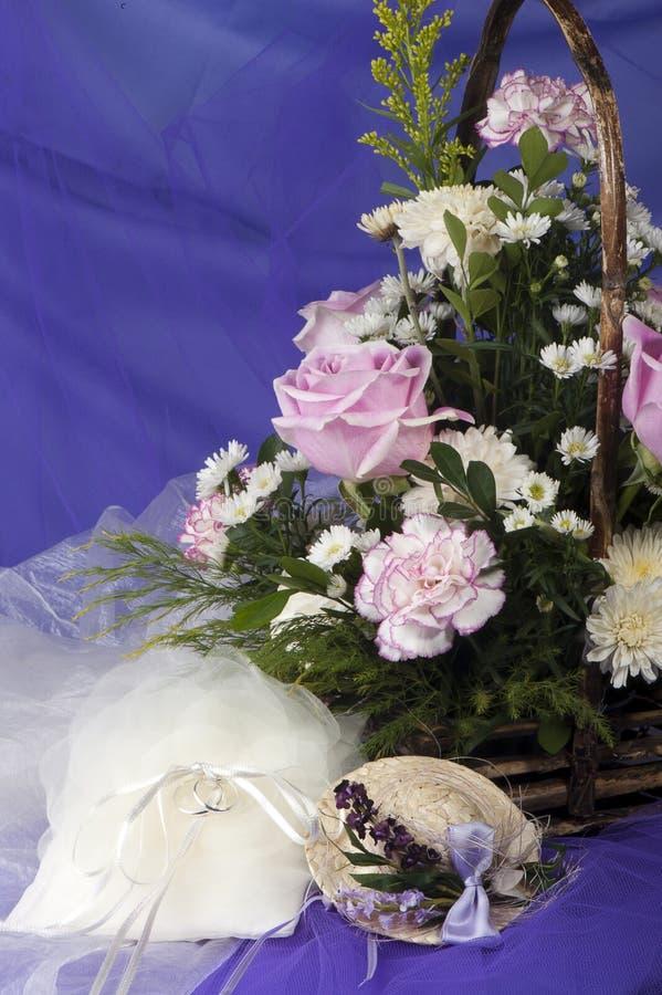 Favores da remoção de ervas daninhas, anéis de casamento e flores imagem de stock