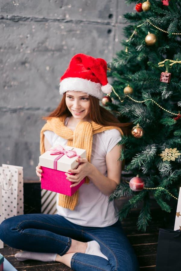 Favorit- ferie flicka ska sätta gåvan under trädet arkivfoton