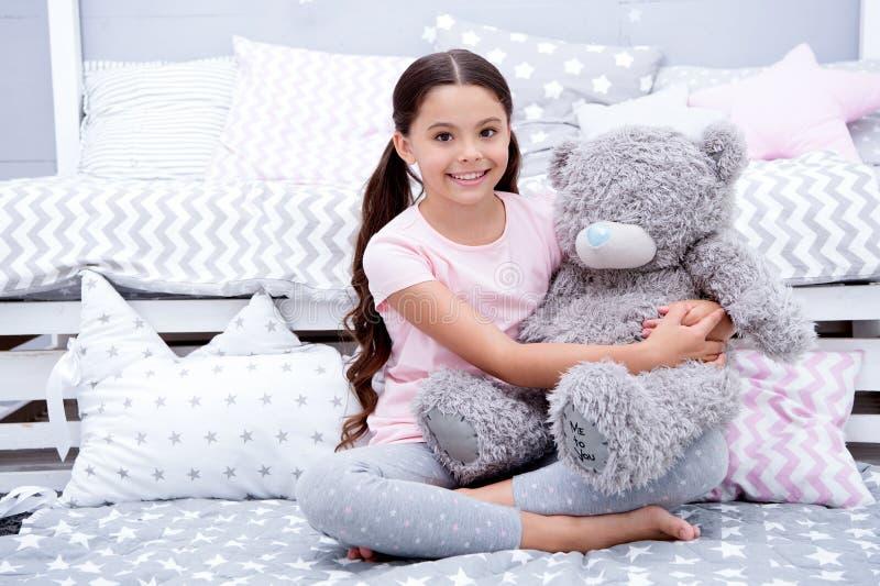Favorit- leksak Flickabarnet sitter på björn för sängkramnalle i hennes sovrum Ungen förbereder sig att gå att bädda ned Angenäm  fotografering för bildbyråer