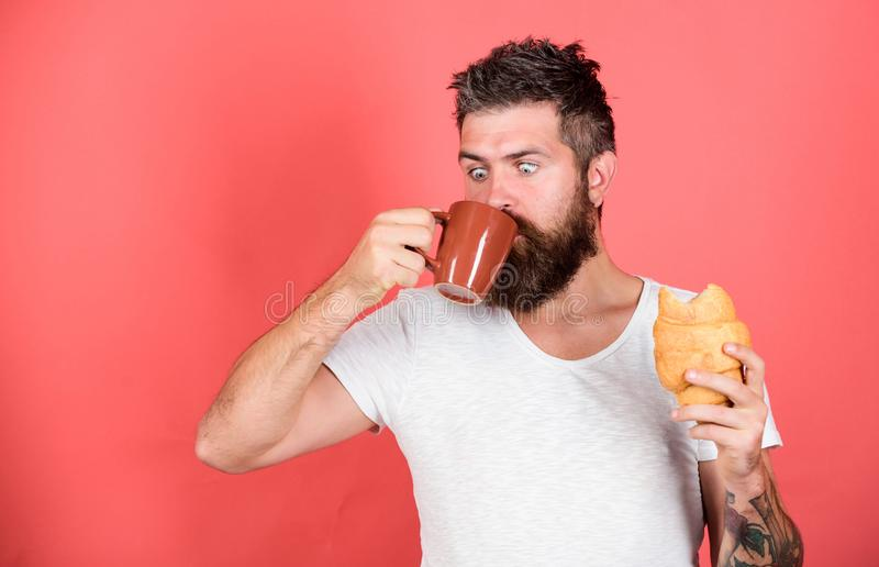 Favorite breakfast. Bearded hipster enjoy breakfast drink coffee. Morning tradition concept. Fresh baked croissant royalty free stock photos
