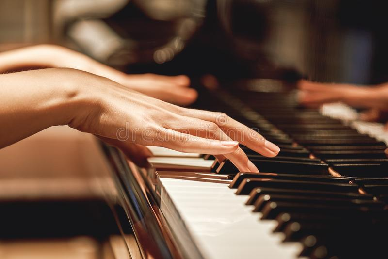 Favorite classical music...Close up view of gentle female hands playing a melody on piano while taking piano lessons stock photography