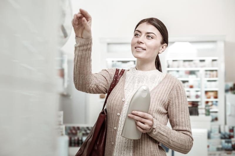 Green-eyed woman feeling pleased after finding her favorite hair shampoo royalty free stock image