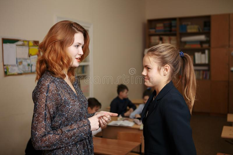 Favorite teacher. Beautiful cute little girl smiling at her teacher during the lesson school courses creativity learning stock photo