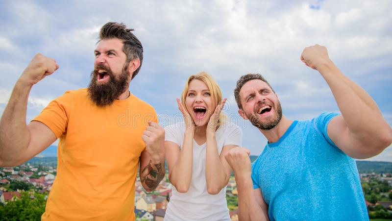 Favorite team won competition. Woman and men look successful celebrate victory sky background. Threesome stand happy royalty free stock photos