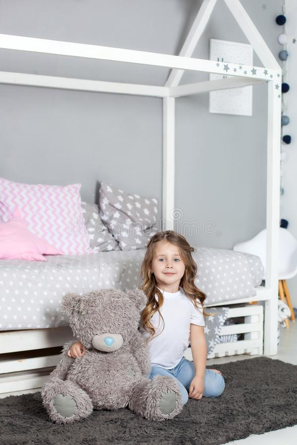 Favorite toy. Girl child sit on bed hug teddy bear in her bedroom. Kid prepare to go to bed. Pleasant time in cozy bedroom. Girl k royalty free stock photos