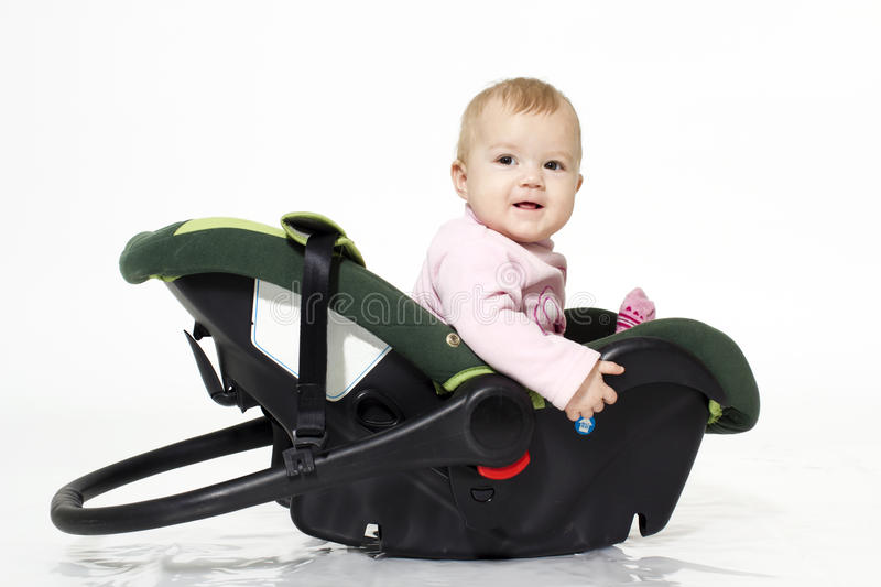 In a favourite cradle. The little girl sits in an automobile cradle stock image