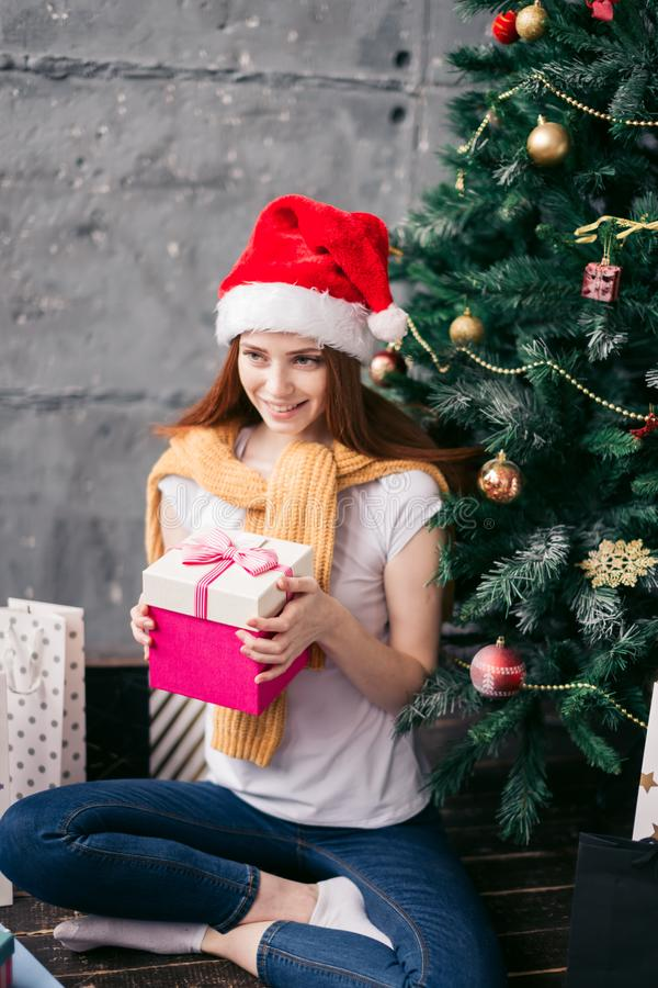 Favourite holiday , girl is going to put the gift under the tree stock photos