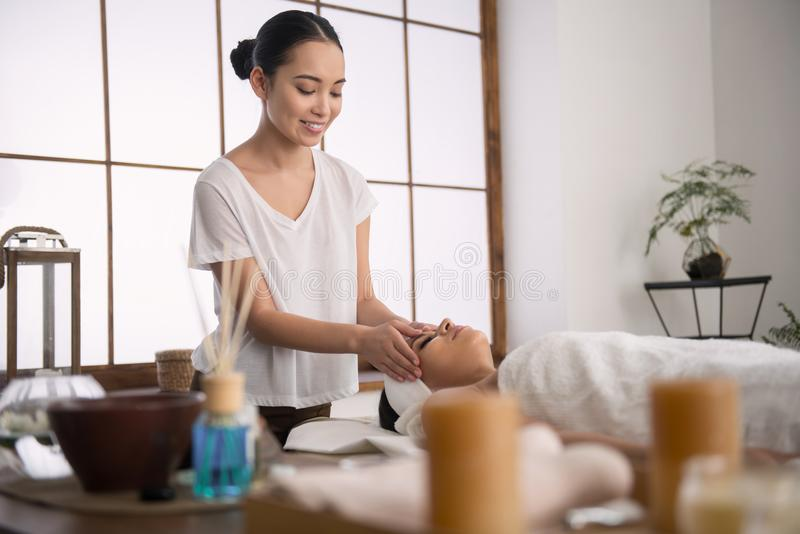Cheerful young masseuse smiling stock photos