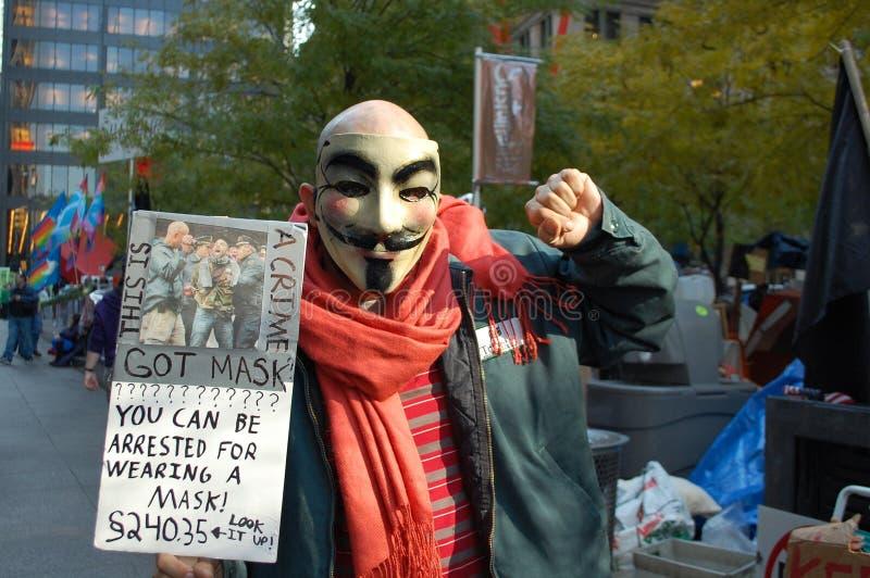 fawkesgrabbmaskeringen upptar protestorgataväggen arkivbild