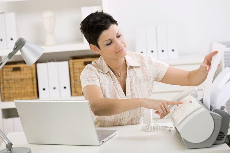 faxmaskin genom att använda kvinnan arkivbild
