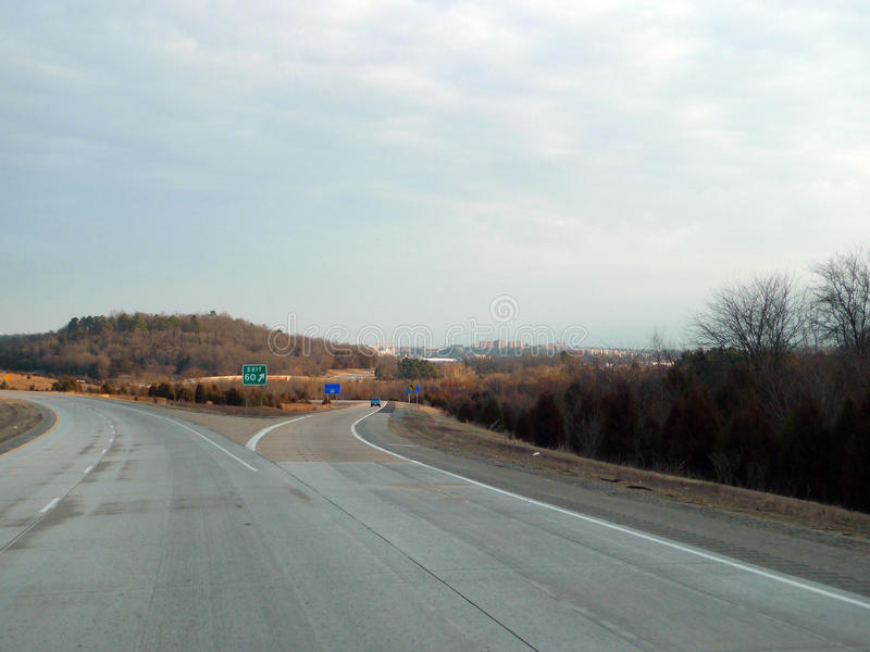 Fayetteville, Arkansas Highway 49, Exit 60. The city of Fayetteville is in the distance at highway 49 exit 60 on a cool spring morning. Landscape background stock photography