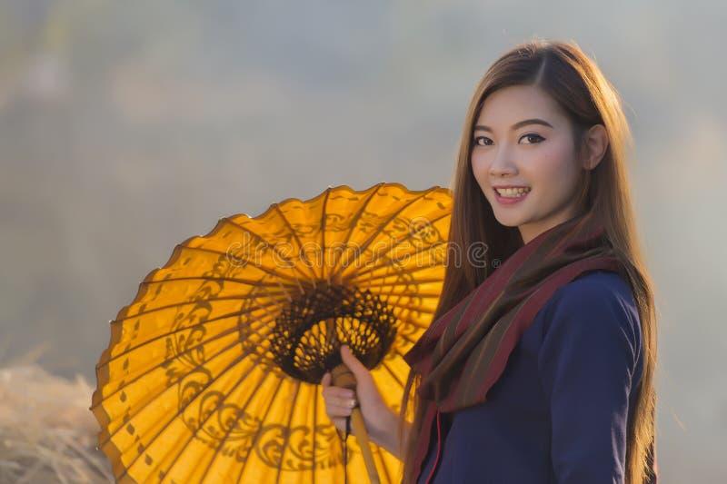 Fazendeiro bonito tailandês da mulher do retrato que mantém o guarda-chuva exterior, campo Tailândia foto de stock