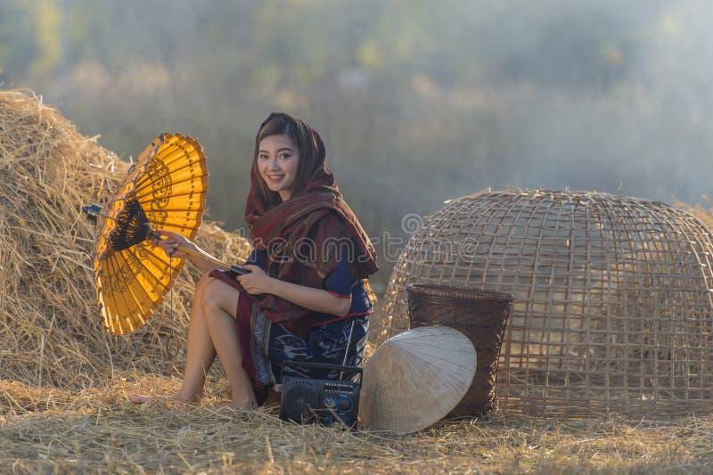 Fazendeiro bonito tailandês da mulher do retrato que mantém o guarda-chuva exterior, campo Tailândia fotografia de stock