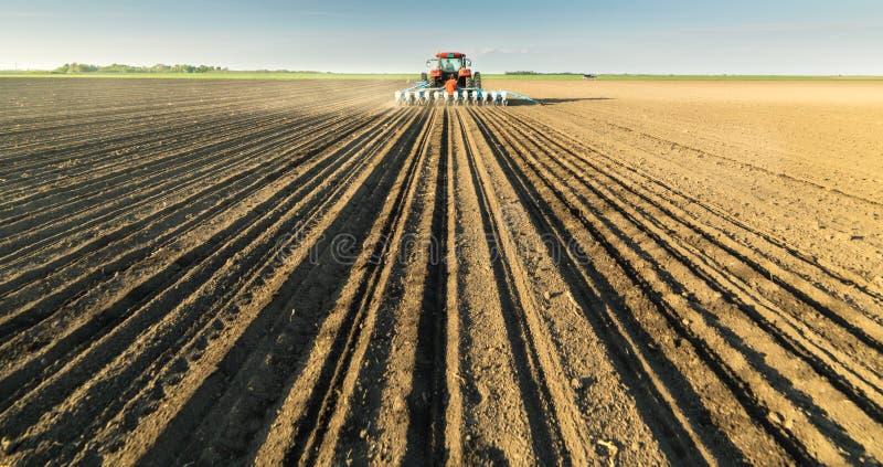 Fazendeiro com o trator que semeia colheitas da soja no campo agr?cola imagens de stock