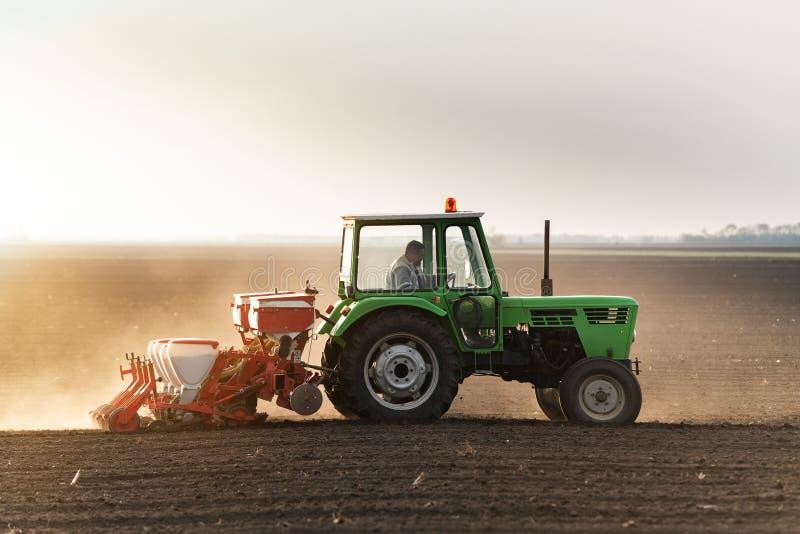 Fazendeiro com o trator que semeia colheitas da soja no campo agr?cola imagem de stock royalty free