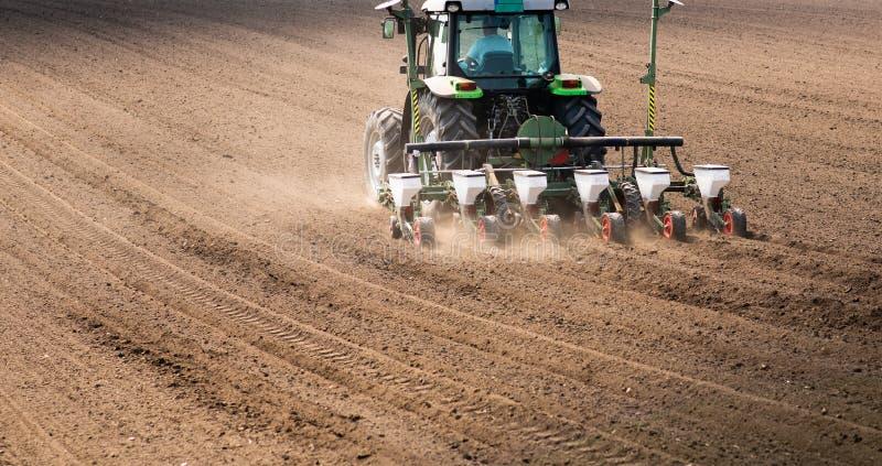 Fazendeiro com o trator que semeia semeando colheitas no campo agr?cola imagem de stock royalty free