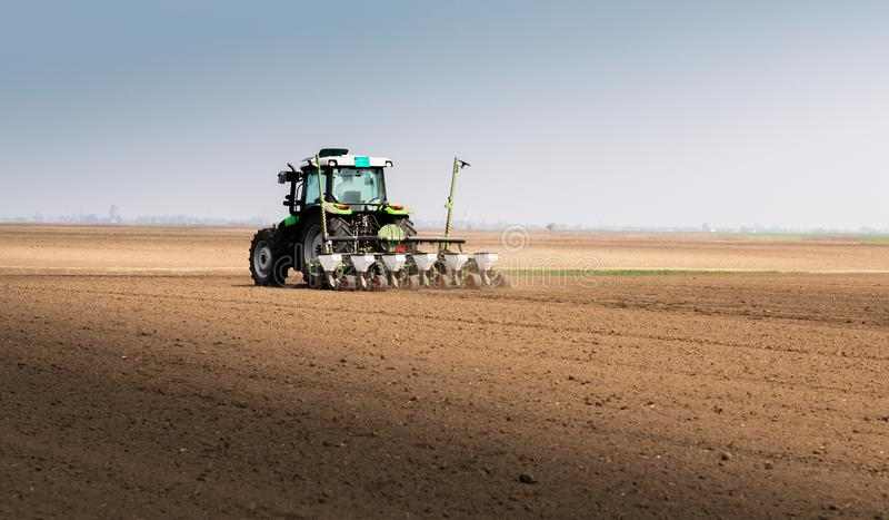 Fazendeiro com o trator que semeia semeando colheitas no campo agr?cola imagens de stock