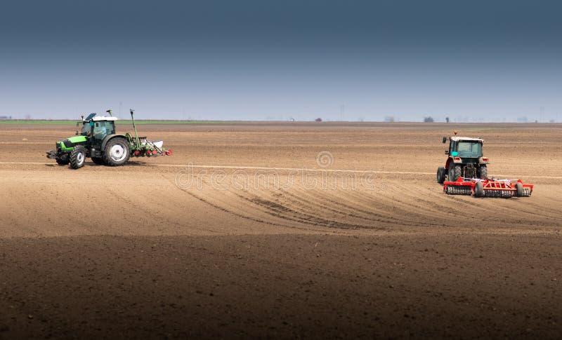 Fazendeiro com o trator que semeia semeando colheitas no campo agr?cola imagens de stock royalty free