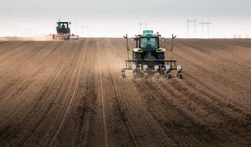 Fazendeiro com o trator que semeia semeando colheitas no campo agr?cola fotografia de stock royalty free