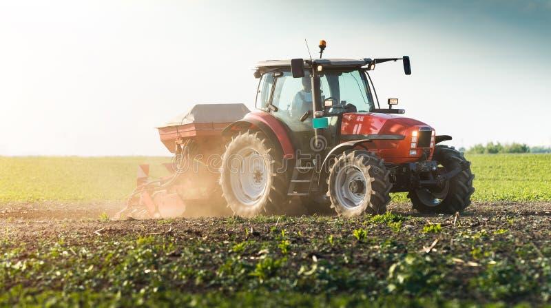 Fazendeiro com semeação do trator - a sementeira colhe no campo agrícola imagem de stock royalty free