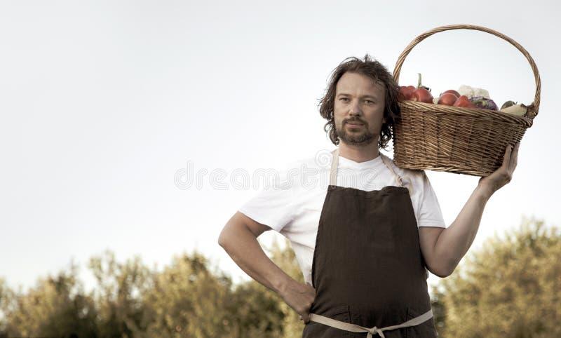 Fazendeiro com uma colheita ecol?gica dos vegetais em uma cesta perto das camas do jardim no ver?o fotos de stock