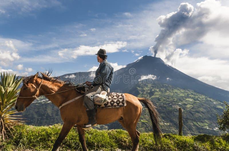 Fazendeiro em um cavalo que olha a erupção de Tungurahua foto de stock royalty free