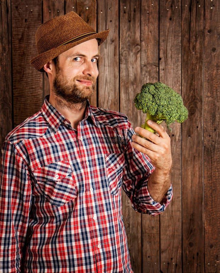 Fazendeiro feliz que guarda brócolis na madeira rústica fotos de stock royalty free