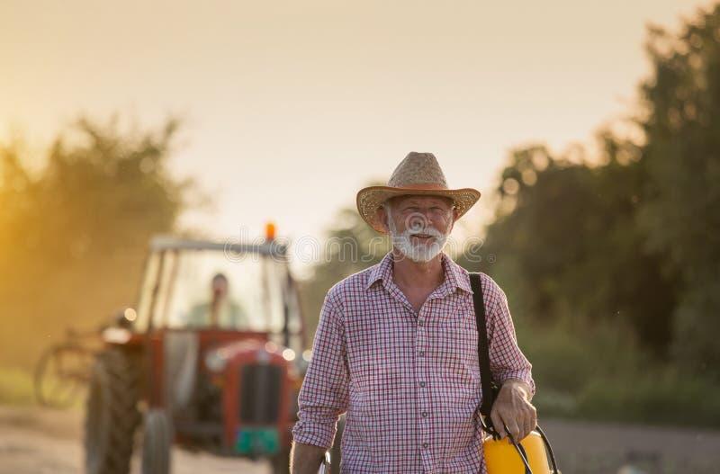 Fazendeiro maduro com pulverizador de plantas na estrada de terra imagem de stock