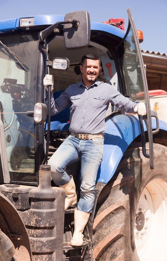 Fazendeiro maduro perto do trator imagem de stock royalty free