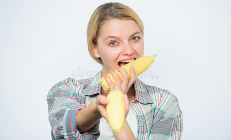 Fazendeiro na colheita de milho que cultiva, menina da mulher do fazendeiro com milho Mulher feliz que come o milho colheita vege fotos de stock