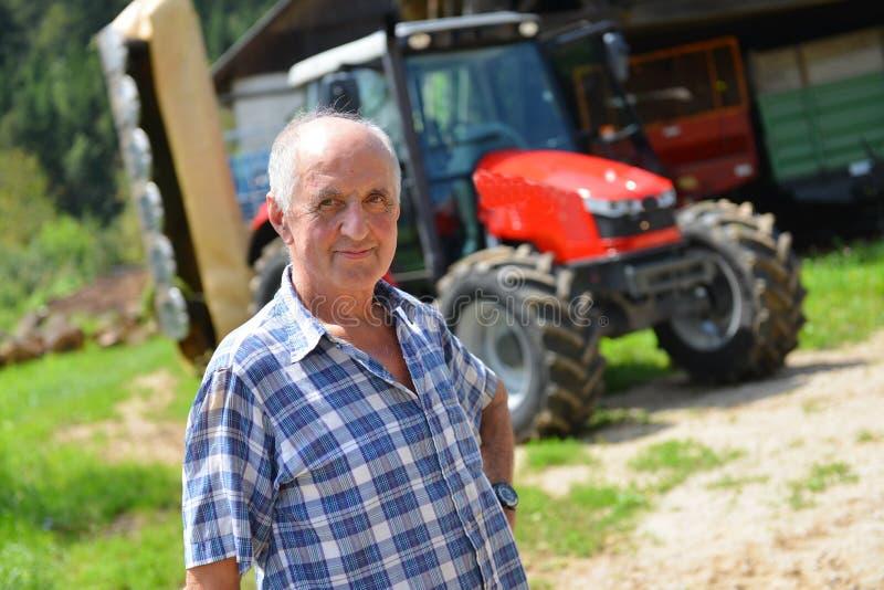 Fazendeiro orgulhoso que está na frente de seu trator fotografia de stock royalty free