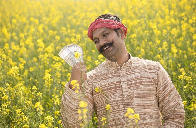Fazendeiro que guarda notas da rupia indiana no campo imagem de stock royalty free