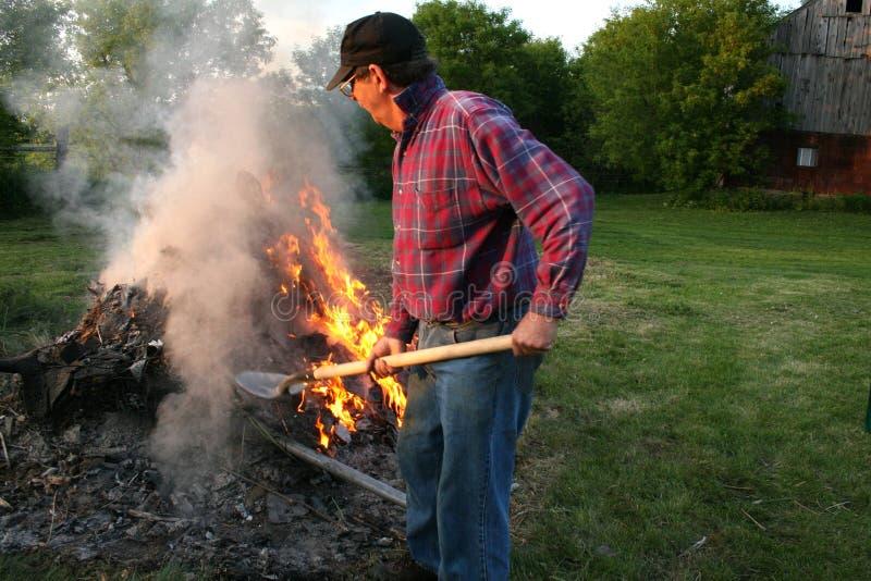 Fazendeiro que presta atenção sobre um incêndio foto de stock royalty free